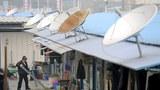 2008年法新社圖片:四川汶川地震後災民臨時住處。棚屋上架着衛星天線。(AFP PHOTO/LIU Jin)